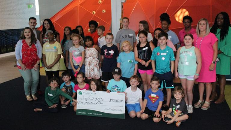 groups of kids standing in front of a $10,000 check